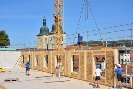 Monks build the largest straw bale building in southern Germany with their own wood and straw.